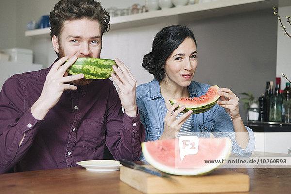 Portrait,Fröhlichkeit,Küche,jung,Wassermelone,essen,essend,isst,Tisch
