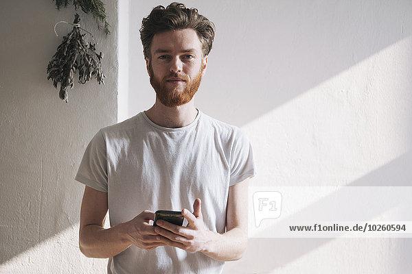 Porträt eines selbstbewussten jungen Mannes mit Handy zu Hause