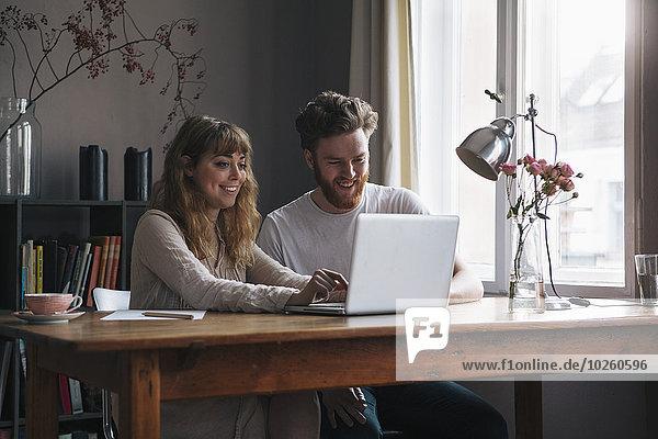 Junges Paar mit Laptop am Tisch am Fenster