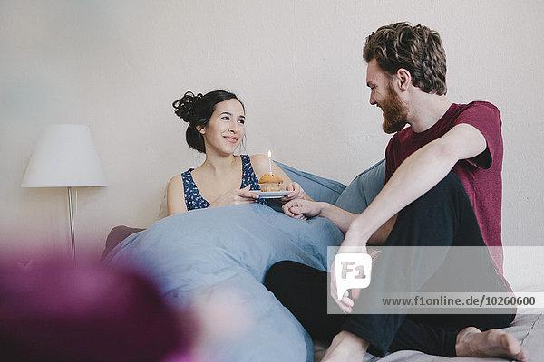Glückliche junge Frau hält Geburtstagskuchen mit Kerze  während sie den Mann im Bett anschaut