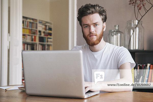 Porträt eines selbstbewussten jungen Mannes mit Laptop am Tisch