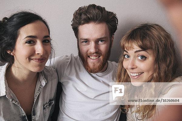 Porträt eines lächelnden jungen Mannes mit Freundinnen  die ihre Freizeit zu Hause verbringen.