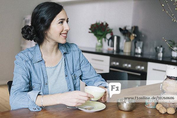 Fröhliche junge Frau beim Kaffeetrinken in der Küche
