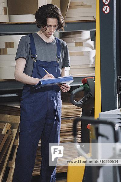 Junges handwerkliches Schreiben auf Papier in einer Fabrik