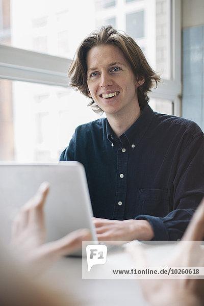 Junger Mann lächelt Kollegen an  während er den Laptop am Tisch benutzt.
