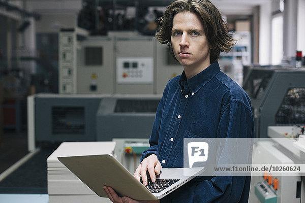 Porträt eines selbstbewussten jungen Technikers mit Laptop in der Fabrik