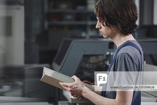 Seitenansicht eines jungen Handwerkers bei der Untersuchung von Kartonbögen in der Fabrik