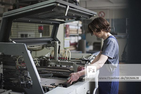 Seitenansicht der jungen Handarbeitermaschine in der Fabrik