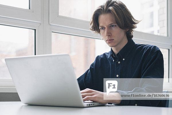 Sicherer junger Mann mit Laptop am Schreibtisch
