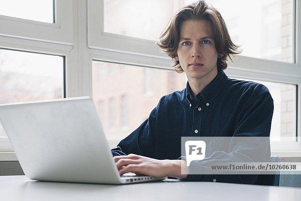 Porträt eines selbstbewussten jungen Mannes mit Laptop am Schreibtisch