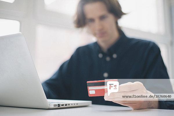 Junger Mann mit Kreditkarte und Laptop am Schreibtisch