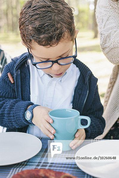 Junge mit Kaffeetasse am Tisch im Wald