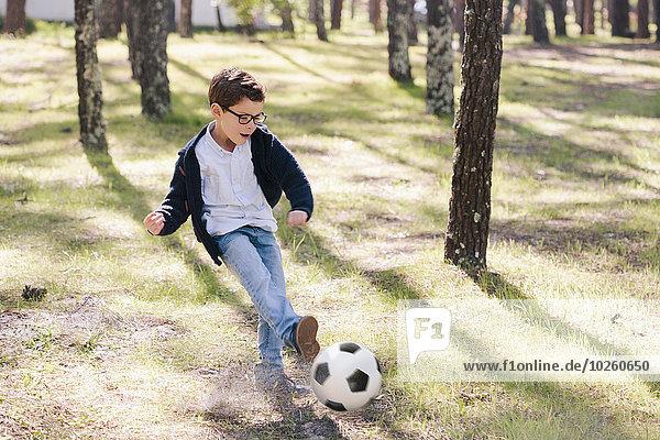 Volle Länge des fröhlichen Jungen beim Fußballspielen im Wald