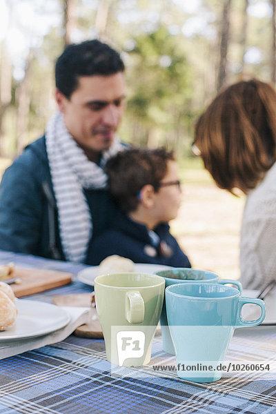 Familie sitzt am Frühstückstisch im Wald