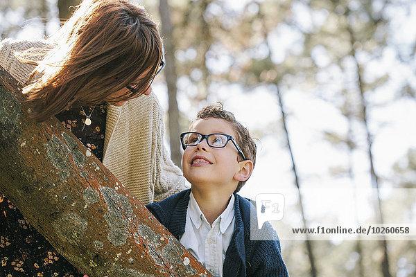 Liebevolle Mutter und Sohn schauen sich im Wald an.