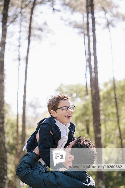 Glücklicher Mann  der den Jungen im Wald hebt.