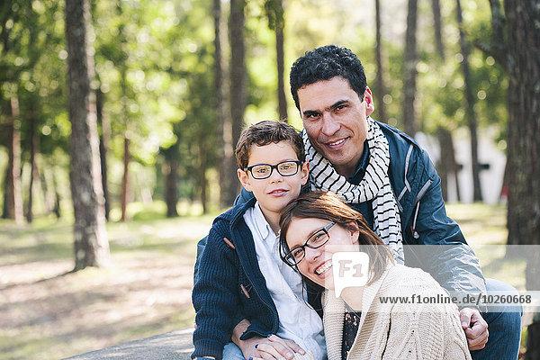 Porträt einer glücklichen Familie  die im Wald sitzt.