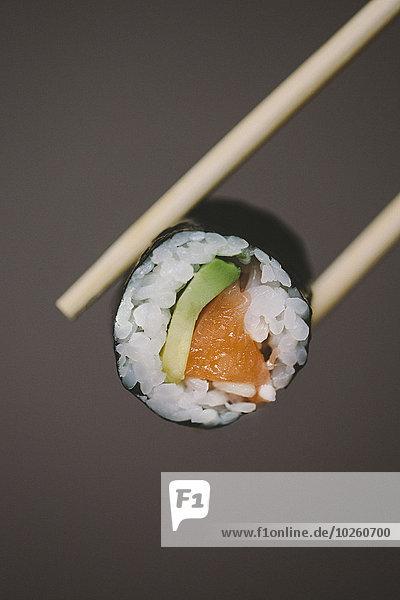 Essstäbchen mit Sushi auf grauem Hintergrund
