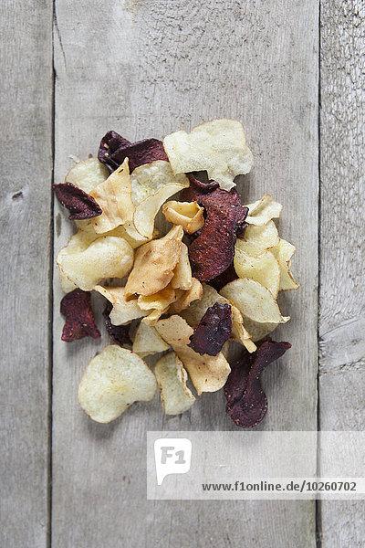 Direkt über Schuss Kartoffel- und Rote-Beete-Chips auf Holztisch