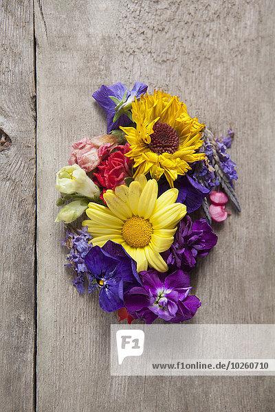 Direkt über der Aufnahme verschiedener Blumen auf Holztisch