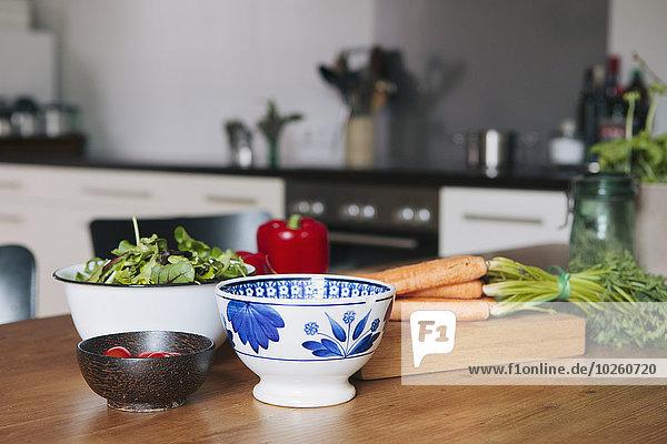 Gemüse und Schalen auf Holztisch in der Küche