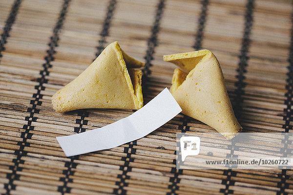 Gebrochener Glückskeks auf Bambusmatte