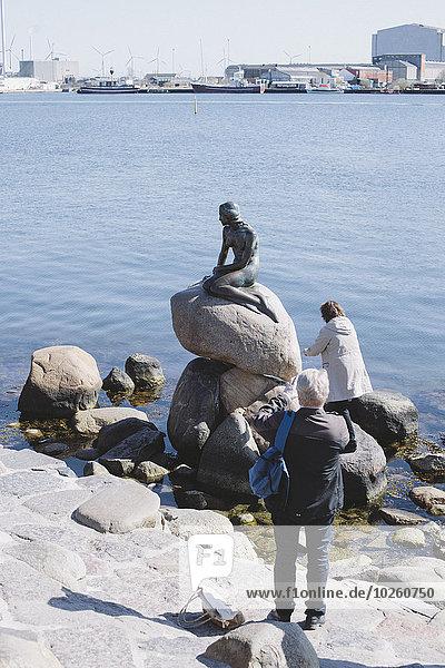 Menschen am Seeufer mit Statue auf Felsen