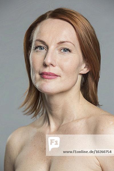 Portrait der oben ohne reifen Frau vor grauem Hintergrund