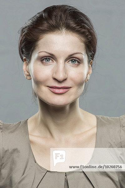 Porträt einer lächelnden mittleren erwachsenen Frau vor grauem Hintergrund