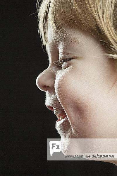 Nahaufnahme des glücklichen Jungen vor schwarzem Hintergrund