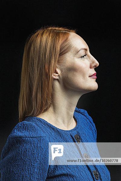 Selbstbewusste reife Frau vor schwarzem Hintergrund