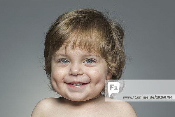 Porträt des glücklichen Jungen vor grauem Hintergrund