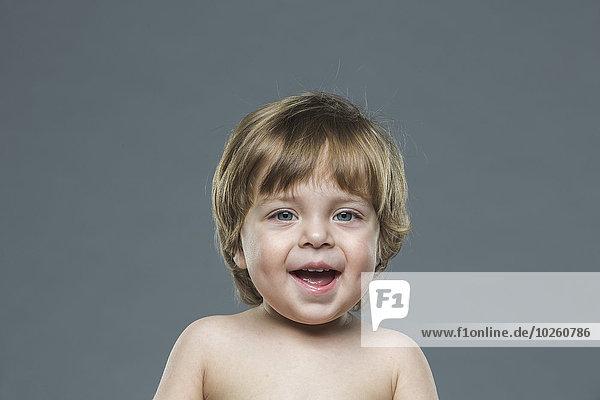 Porträt des fröhlichen Jungen vor grauem Hintergrund