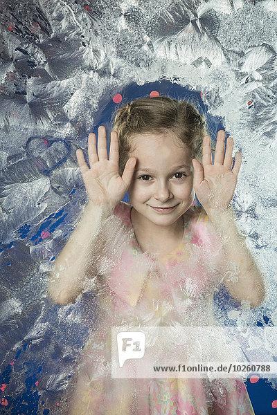 Porträt eines süßen Mädchens  das sich auf gefrorenes Glas stützt.