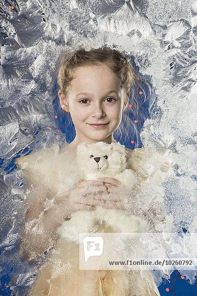 Porträt eines süßen Mädchens mit Teddybär gegen gefrorenes Glas