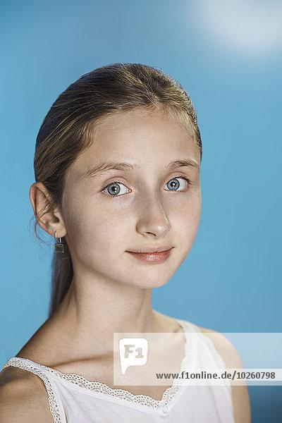 Nahaufnahme des süßen Mädchens vor blauem Hintergrund