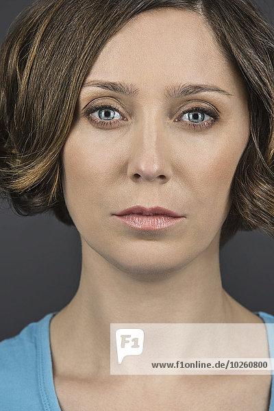Nahporträt einer ernsthaften Frau vor grauem Hintergrund