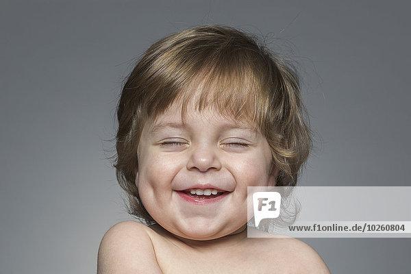 Nahaufnahme des fröhlichen Jungen mit geschlossenen Augen über grauem Hintergrund
