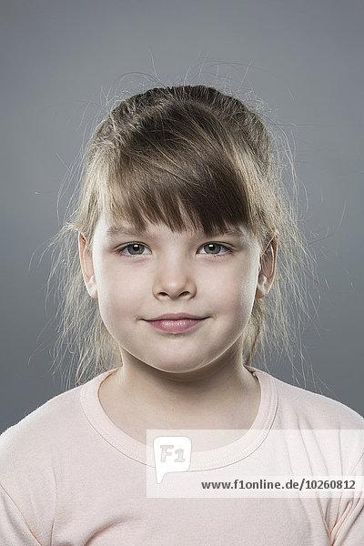 Porträt des süßen Mädchens vor grauem Hintergrund