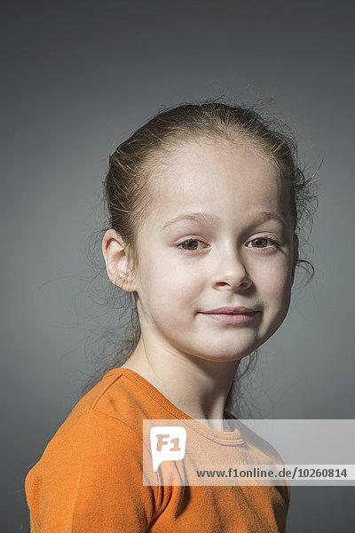 Porträt des lächelnden Mädchens vor grauem Hintergrund