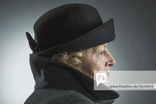 Seitenansicht der Seniorin mit Hut und Jacke vor grauem Hintergrund