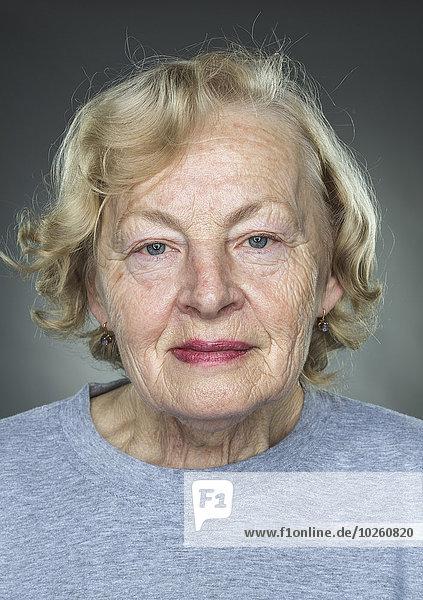 Nahaufnahme des Porträts einer älteren Frau vor grauem Hintergrund