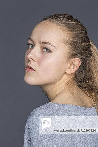 Seitenansicht Porträt eines selbstbewussten Teenagermädchens vor grauem Hintergrund