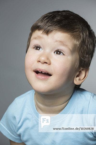 Überraschter Junge  der vor grauem Hintergrund aufblickt
