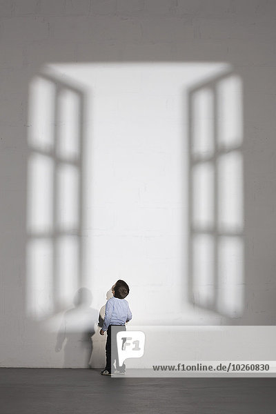 Junge schaut auf den Schatten des offenen Fensters an der weißen Wand zu Hause.