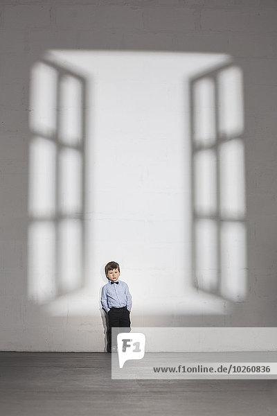 Schatten eines offenen Fensters  das auf den Jungen fällt  der zu Hause an der weißen Wand steht.