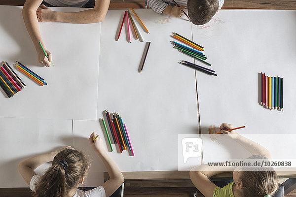 Hochwinkelansicht der Kinder beim Zeichnen auf Papieren am Tisch