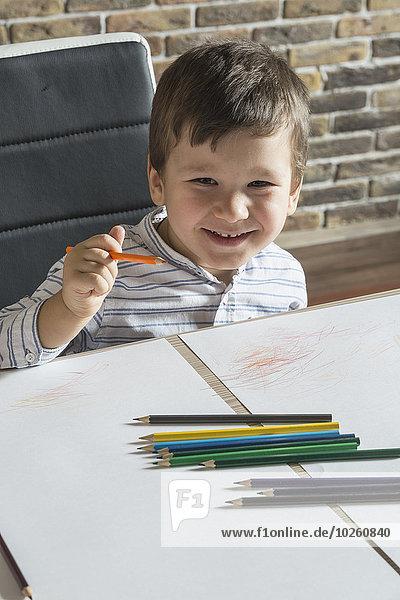 Porträt des glücklichen Jungen beim Zeichnen am Tisch im Haus