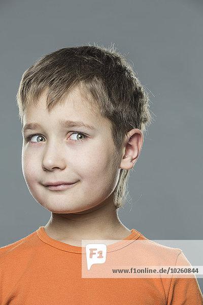 Nachdenklicher Junge  der vor grauem Hintergrund wegschaut.