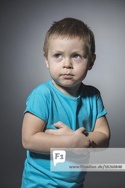 Wütender Junge schaut weg  während er die Arme vor grauem Hintergrund kreuzt.